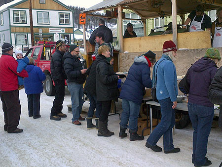 Festival goers line up to get their BBQed chow from served by the Dawson City Volunteer Fire Department.