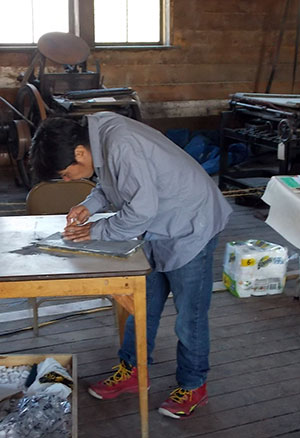 Nunavut artist Ashoona Ashoona carves a block to be used for stone-cut printmaking at the Dawson Daily News Print & Publishing Symposium.