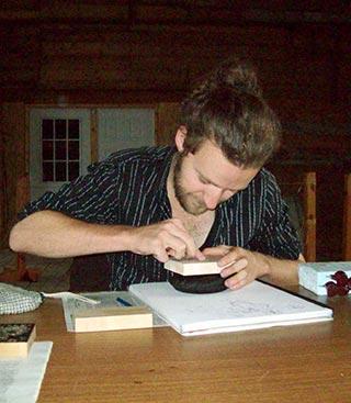 Mathias MacPhee works on carving a woodcut for block printing.