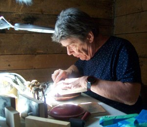 Basking in the glorious sunshine the weekend offered, John Steins works on carving a wood block used for printing.