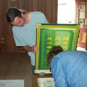 Taking a break from his papermaking workshop, Nathaniel Marchand helps the Silkscreen Club.